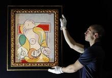 Работник Sotheby's держит в руках полотно Пабло Пикассо в аукционном доме в Лондоне, 31 января 2011 г. Полиция Сербии обнаружила два полотна Пабло Пикассо, украденные в 2008 году из галереи в Швейцарии, сообщил министр внутренних дел Сербии Ивица Дачич в среду. REUTERS/Luke MacGregor