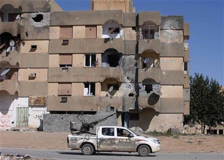 A vehicle for fighters with Libya's interim government patrols in front of a damaged building in Bani Walid October 18, 2011. REUTERS/Ismail Zitouny