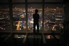 <p>A man watches the skyline of Shanghai from the Shanghai Financial Center building, October 25, 2011. REUTERS/Carlos Barria</p>