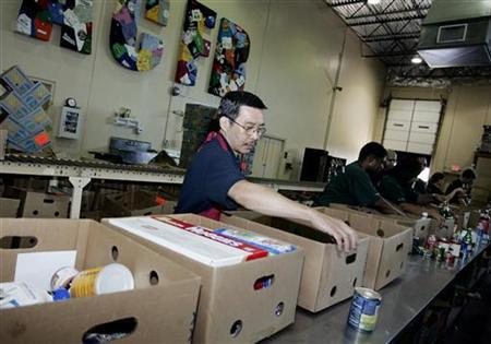 Volunteer Nam Nguyen (L), sorts items in the product resource center at the Atlanta Community Food Bank in Atlanta, Georgia in this picture taken June 4, 2008.   REUTERS/Tami Chappell