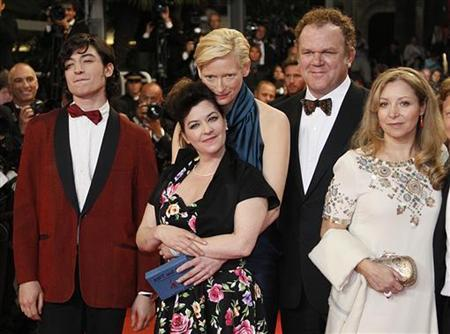 Director Lynne Ramsay (2nd,R) and cast members Ezra Miller (L), Tilda Swinton (3rd,L), John C. Reilly (2nd,R)  pose with an unidentified guest as they arrive on the red carpet for the screening of the film ''We Need To Talk About Kevin'', in competition at the 64th Cannes Film Festival, May 12, 2011.      REUTERS/Yves Herman