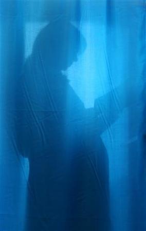 A pregnant woman is seen through a curtain in a file photo. REUTERS/Mykhailo Markiv