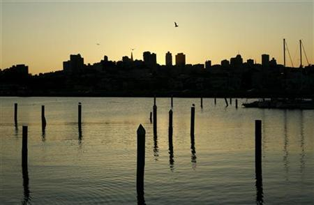 The sun begins to rise over the skyline and San Francisco Bay in San Francisco, California November 13, 2009.    REUTERS/Robert Galbraith