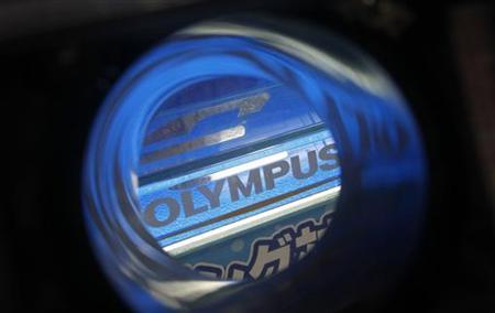 Olympus's logo is seen through its waterproof housing at an electronics shop in Tokyo October 20, 2011.    REUTERS/Kim Kyung-Hoon