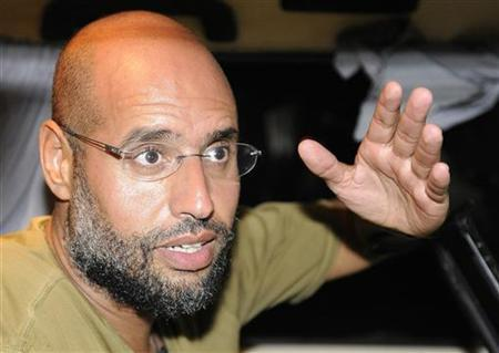 Saif Al-Islam, son of Libyan leader Muammar Gaddafi, gestures as he talks to reporters in Tripoli, August 23, 2011.   REUTERS/Paul Hackett