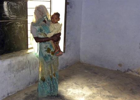 Phul Kumari, 25, stands with her child in front of a window in a village community centre in Baghpat district, located in Uttar Pradesh October 18, 2011. REUTERS/TrustLaw/Nita Bhalla