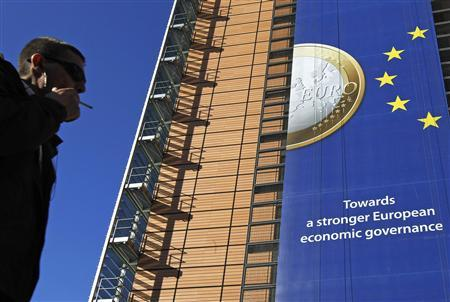 A banner featuring a Euro coin is seen on the European Commission headquarters building ahead of a European Union heads of state summit in Brussels October 26, 2011. REUTERS/Yves Herman