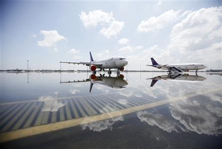 Airplanes are seen parked on a flooded tarmac at Don Muang airport in Bangkok October 26, 2011.  REUTERS/Bazuki Muhammad