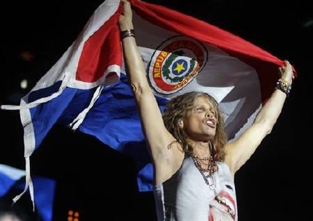 Steven Tyler, the lead singer of rock band Aerosmith, with a Paraguayan national flag performs during a concert on the first stop of their Latin America tour at the Jockey Club in Asuncion, October 26, 2011. REUTERS/Jorge Adorno