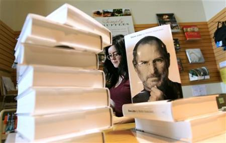 Store clerk Allison Page stacks the new biography of Apple CEO Steve Jobs by Walter Isaacson in San Francisco, California October 24, 2011. REUTERS/Robert Galbraith