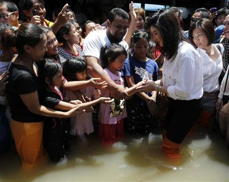 Thailand's Prime Minister Yingluck Shinawatra (front R) greets people as she visits a flooded area in Nonthaburi province on the outskirts of Bangkok September 18, 2011. REUTERS/Sukree Sukplang
