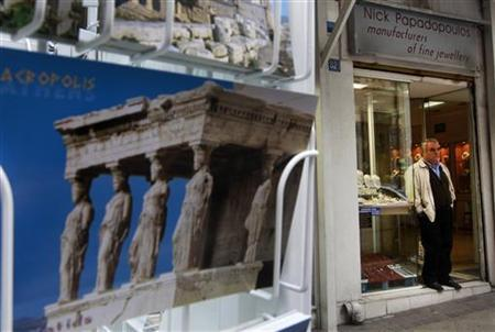 A shop owner stands at the entrance of his empty shop in central Athens October 27, 2011. REUTERS/ John Kolesidis