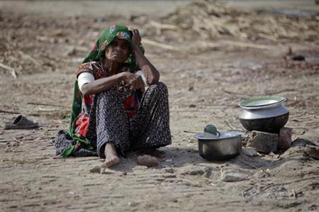 Kamani, 70, who has been displaced by floods, prepares food outside her tent after escaping from a flooded village in the Badin district of Pakistan's Sindh province September 20, 2011.  REUTERS/Akhtar Soomro