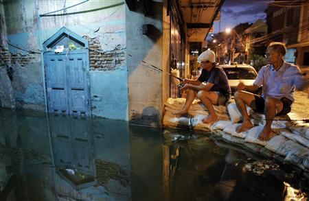 Residents fish from a sandbag barrier built to protect their neighborhood from floods advancing into central Bangkok October 28, 2011.REUTERS/Damir Sagolj