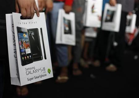 Customers hold their newly purchased Samsung Galaxy S2 android phone in Jakarta July 23, 2011. REUTERS/Beawiharta