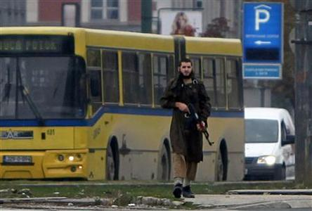 A gunman with an automatic weapon walks in Sarajevo, after he fired shots at the U.S. embassy, October 28, 2011.  REUTERS/Dado Ruvic