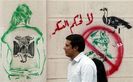 A man walks past a graffiti depicting Field Marshal Mohamed Tantawi, the head of the ruling Supreme Council of the Armed Forces (SCAF), in downtown Cairo, September 23, 2011. The writing on the wall reads: ''No to Military Rule''(top) and ''Donkey''.REUTERS/Amr Abdallah Dalsh