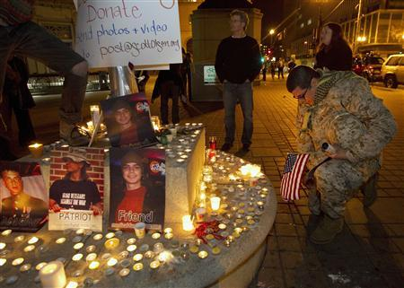 A soldier kneels with an American flag in front of a candle-lit memorial in support of Scott Olsen at City Hall in Oakland October 27, 2011.  REUTERS/Kim White