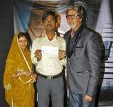 <p>Sushil Kumar (C) and his wife pose with Bollywood actor Amitabh Bachchan (R) after Kumar won about $1 million on an Indian game show in Mumbai October 25, 2011. REUTERS/Stringer</p>