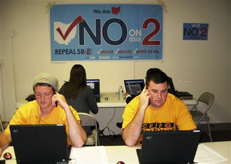 Firefighters Thomas Eickelberger (L) and Todd Schlenk work at a phone bank urging voters to vote against a bill that limits collective bargaining rights for public safety in Hamilton, Ohio, October 20, 2011.  REUTERS/Mary Wisniewski