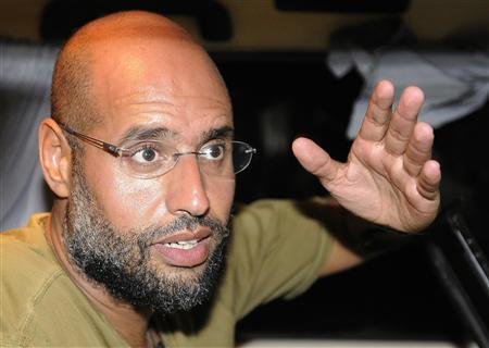 Saif Al-Islam, son of Libyan leader Muammar Gaddafi, gestures as he talks to reporters in Tripoli August 23, 2011.  REUTERS/Paul Hackett/Files