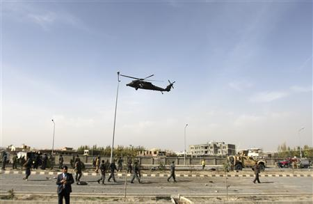 A NATO helicopter flies over the site of a bomb blast in Kabul October 29, 2011.   REUTERS/Mohammad Ismail