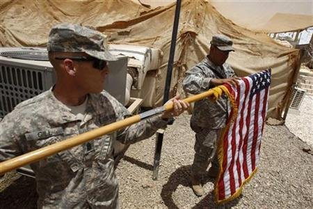 U.S. soldiers fold their national flag as they prepare to hand over their base to Iraqi forces in Iraq's southern province of Basra June 22, 2011.  REUTERS/Atef Hassan