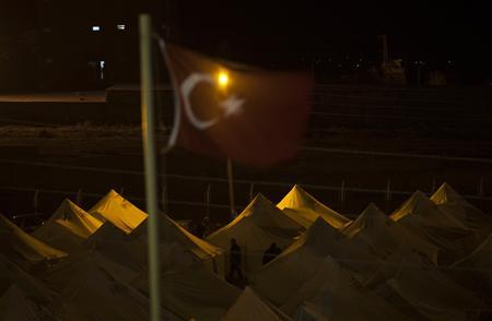 Turkey's national flag is seen near a stadium currently used as a relief shelter campsite for earthquake survivors in Ercis October 29, 2011. REUTERS/Morteza Nikoubazl