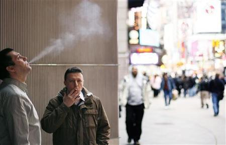 A pair of smokers stand outside of an office building in the Times Square region of New York April 1, 2009.  REUTERS/Lucas Jackson