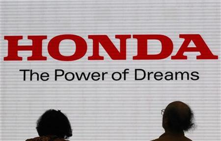 Visitors are silhouetted against a Logo of the Honda Motor at the company showroom in Tokyo October 31, 2011.  REUTERS/Issei Kato