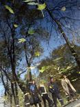 Отражение прохожих, гуляющих по парку в Киеве, 26 октября 2011 года. Короткая рабочая неделя в Москве будет такой же, как и минувшие выходные - прохладной, но без заморозков, ожидают синоптики. REUTERS/Alexandr Kosarev