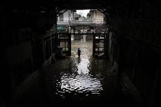 Женщина покидает затопленный рынок в центре Бангкока, 31 октября 2011 г. Власти Таиланда надеются, что затопленные в результате наводнения заводы возобновят свою работу в течение трех месяцев после спада воды, сказала премьер-министр страны Йинглак Чиннават в понедельник.REUTERS/Damir Sagolj