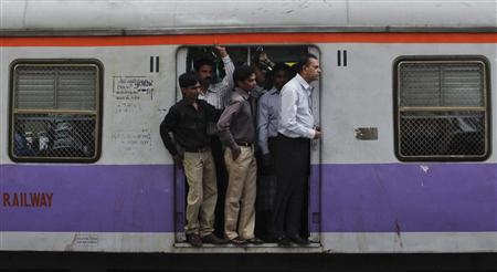 Commuters stand at the open doorway of a suburban train during the morning rush hour in Mumbai, October 31, 2011.  REUTERS/Danish Siddiqui