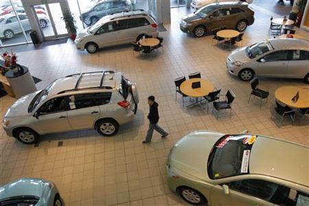 A customer looks over Toyota automobiles at a dealership in Daly City, California February 2, 2010.  REUTERS/Robert Galbraith