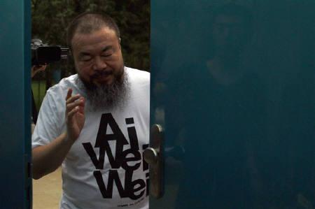 Dissident Chinese artist Ai Weiwei closes the door to his studio after speaking to the media in Beijing June 23, 2011. REUTERS/David Gray/Files