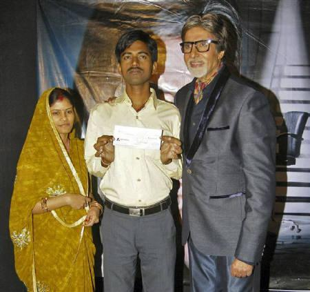 Sushil Kumar (C) and his wife pose with Bollywood actor Amitabh Bachchan (R) after Kumar won about $1 million on an Indian game show in Mumbai October 25, 2011. REUTERS/Stringer