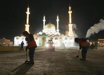 """Уборщики чистят площадь перед мечетью Нур-Астана в Астане 10 января 2006. Исламистская группировка """"Джунд аль-Халифат"""" взяла на себя ответственность за взрывы в городе Атырау на западе Казахстана, сообщила американская мониторинговая и исследовательская служба. REUTERS/Shamil Zhumatov"""