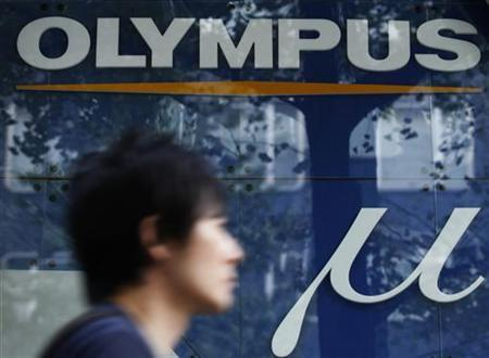 A man walks past an advertisement of Japan's Olympus Corp in Tokyo October 31, 2011. REUTERS/Yuriko Nakao