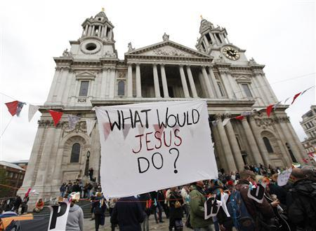 A banner which reads ''What would Jesus do?'' flies outside St. Paul's Cathedral in London October 31, 2011. REUTERS/Suzanne Plunkett