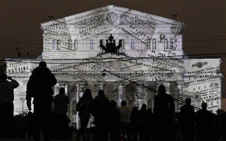 People look at the illuminated Bolshoi Theatre during its reopening ceremony in Moscow, October 28, 2011.  REUTERS/Denis Sinyakov