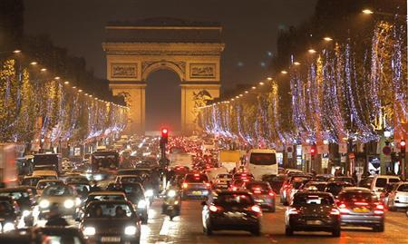 Holiday lights hang from trees to illuminate Champs Elysees in Paris as rush hour traffic fills the avenue leading up to the Arc de Triomphe November 22, 2010. REUTERS/Charles Platiau