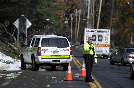 A West Milford fire chief directs traffic around a power line brought down by a tree on Union Valley Road, West Milford, New Jersey, October 30, 2011. REUTERS/Mark Dye