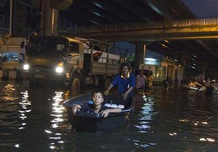 A man uses a boat to transport a boy through the flooded streets of Bang Phlat district in Bangkok on November 1, 2011. REUTERS/Adrees Latif