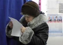Женщина изучает бюллетень на избирательном участке в Ростове-на-Дону, 14 марта 2010 года. Выборы в Государственную думу РФ пройдут 4 декабря. В статье приводится список партий, которые принимают в них участие. REUTERS/Alexey Koverznev
