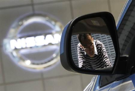 A visitor is reflected on the side mirror of a Nissan Motor car at the company's showroom in Tokyo November 2, 2011. REUTERS/Issei Kato