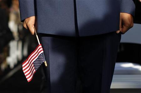 A new U.S. citizen holds an American flag during a naturalization ceremony beneath the Statue of Liberty, October 28,  2011.  REUTERS/Mike Segar