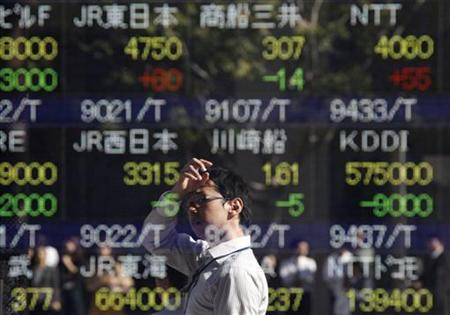 A man is reflected on an electronic board displaying stock prices outside a brokerage in Tokyo October 31, 2011.  REUTERS/Issei Kato