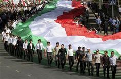 Жители Таджикистана держат гигантский национальный флаг на праздновании Дня независимости в Душанбе, 9 сентября 2011 г. Таджикистан в ближайшие три года планирует привлечь кредиты на общую сумму $1,241 миллиарда, сохранив при этом отношение внешнего долга к ВВП на уровне, не вызывающем опасений международных кредиторов, сообщил в среду министр финансов. REUTERS/Stringer