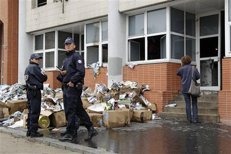 French police stand in front of the damaged offices of French satirical magazine Charlie Hebdo in Paris November 2, 2011. The magazine's offices were set on fire in the early hours of Wednesday, its editor told Europe 1 radio. The attack took place after the magazine published an edition it said was guest-edited by the Prophet Mohammed and was renamed ''Charia Hebdo'', in a reference to Sharia law, media reported. REUTERS/Benoit Tessier