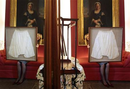 Kate Bain from Lyon and Turnbull auctioneers poses for photographers with a framed pair of silk bloomers undergarments that once belonged to Queen Victoria, during a photocall for the auction of the Forbes Collection in Edinburgh, Scotland October 27, 2011. REUTERS/David Moir